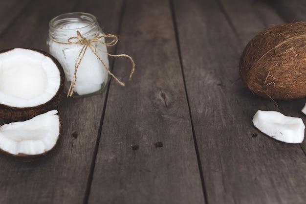 Cocos rotos sobre fondo de madera gris con tarro de aceite de coco virgen extra orgánico crudo.
