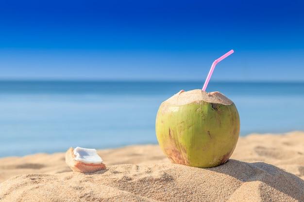 Los cocos verdes dulces riegan con la paja de beber en la playa de la arena en phuket tailandia.