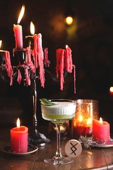 Cóctel agrio verde con albahaca entre velas rojas en el restaurante de la bruja misteriosa