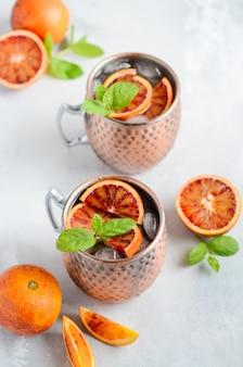 Cóctel del alcohol de la mula de moscú de la naranja de sangre con las hojas y el hielo de menta fresca en las tazas de cobre en un fondo concreto gris.