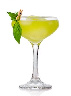 Coctel de alcohol verde con guarnición de albahaca aislado