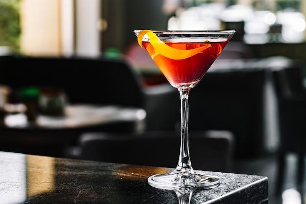 Cóctel de alcohol con vista lateral de cáscara de naranja