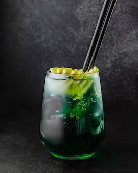 Cóctel de alcohol con vista lateral de hielo de limón