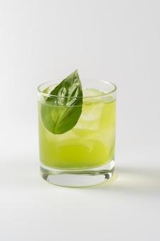 Cóctel alcohólico con albahaca en copa de cristal
