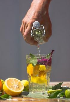 Cóctel alcohólico de albahaca smash gin con hojas frescas de albahaca y cítricos. beber en movimiento congelado, gotas en salpicaduras de líquido, chorro de jugo, rodaja de limón en vuelo. bebida fría de verano