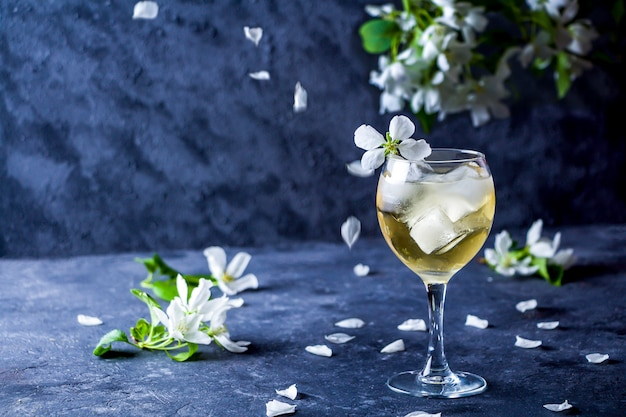 Cóctel alcohólico de apple con vino espumoso en vidrio sobre un fondo oscuro. refrescante bebida fresca de verano, limonada o té helado decorado con pétalos de manzano.