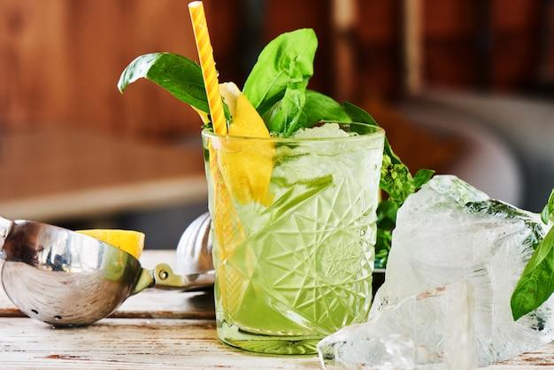 Cóctel alcohólico basil smash en un vaso de vidrio y un trozo de hielo sobre una mesa de madera
