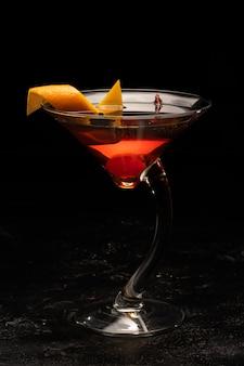 Cóctel alcohólico en copa de vidrio transparente.