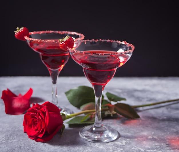Cóctel alcohólico exótico rojo en copas transparentes