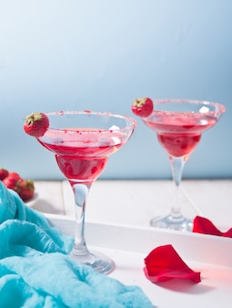 Cóctel alcohólico exótico rojo en vasos transparentes y pétalos de rosas rojas sobre la mesa blanca de madera para una cena romántica.