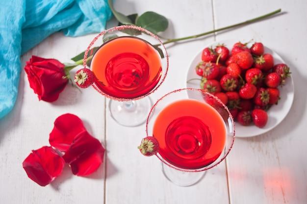Cóctel alcohólico exótico rojo en vasos transparentes, plato con fresas frescas y rosa roja sobre la mesa blanca de madera para una cena romántica.