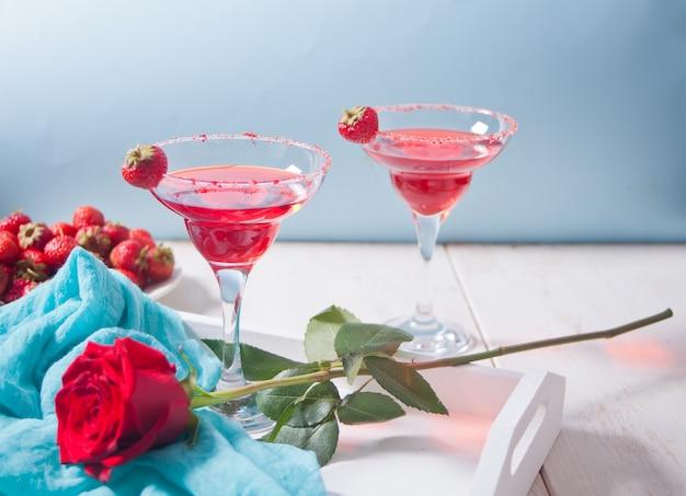 Cóctel alcohólico exótico rojo en vasos transparentes y rosa roja en la bandeja blanca de madera para una cena romántica.