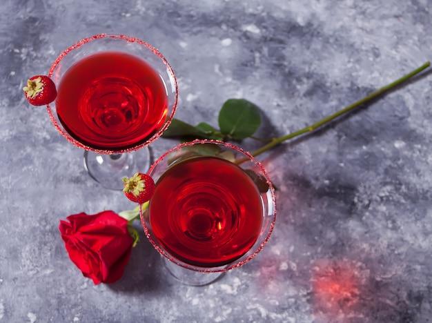 Cóctel alcohólico exótico rojo en vasos transparentes y rosa roja para una cena romántica.