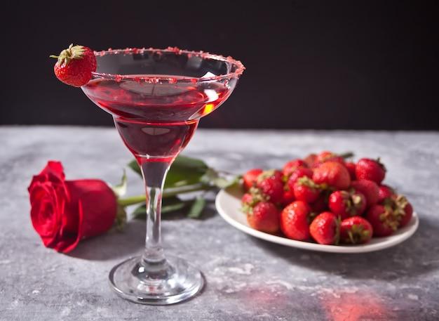 Cóctel alcohólico exótico rojo en vidrio transparente, plato con fresas frescas y rosa roja en el fondo de hormigón para una cena romántica.