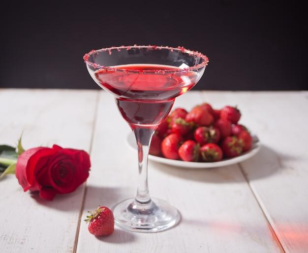 Cóctel alcohólico exótico rojo en vidrio transparente, plato con fresas frescas y rosa roja sobre la mesa blanca de madera para una cena romántica.