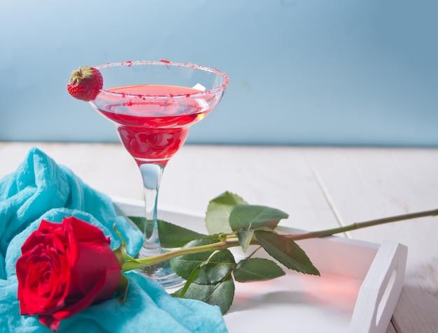 Cóctel alcohólico exótico rojo en vidrio transparente y rosa roja en la bandeja blanca de madera para una cena romántica.