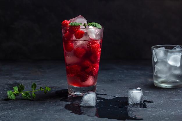 Cóctel alcohólico de frambuesa con licor, vodka, hielo y menta en una pared oscura. mojito de frambuesa. refrescante bebida fría, limonada o té helado en un vaso. cerrar, copiar espacio para texto, bajo perfil