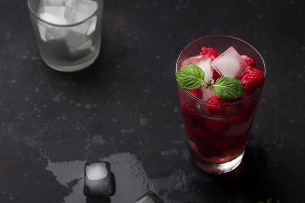 Cóctel alcohólico de frambuesa con licor, vodka, hielo y menta sobre un fondo oscuro. mojito de frambuesa. refrescante bebida fría, limonada o té helado en un vaso, discreto