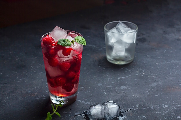 Cóctel alcohólico de frambuesa con licor, vodka, hielo y menta sobre un fondo oscuro. mojito de frambuesa. refrescante bebida fría, limonada o té helado en un vaso.