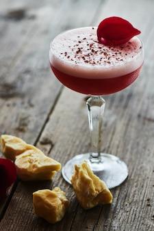 Cóctel alcohólico de frambuesa sauer que consiste en licores, vermut, chispas de chocolate y jugo de limón servido en un vaso de vidrio sobre una mesa de madera.