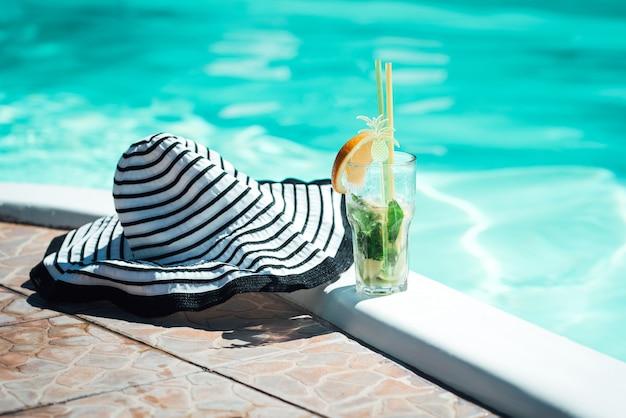 Cóctel alcohólico de frutas a base de lima, menta, naranja, refresco de pie en el borde de la piscina azul