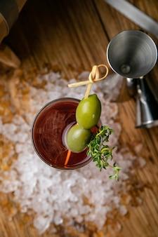 Cóctel alcohólico con hielo, aceitunas en una mesa de madera