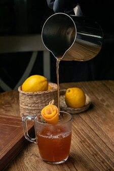 Cóctel alcohólico con hielo, limón en una mesa de madera