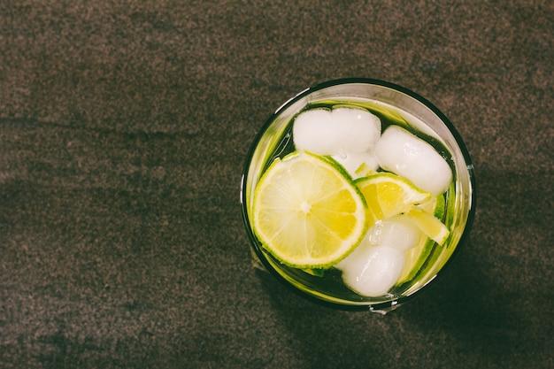 Cóctel alcohólico con limón verde y hielo.
