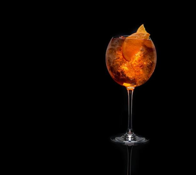 Cóctel alcohólico con rodaja de naranja sobre fondo negro con espacio de copia