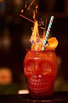 Cóctel alcohólico de zombis que consiste en ajenjo, ron con especias casero, arándano y jugo de toronja en un vaso con forma de calavera