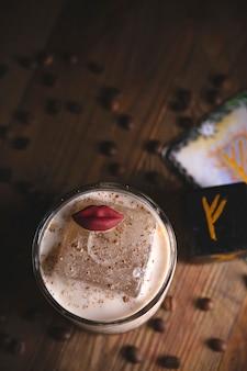 Cóctel amargo de café picante con un gran cubo de hielo y decoración de labios junto a las runas en un restaurante místico