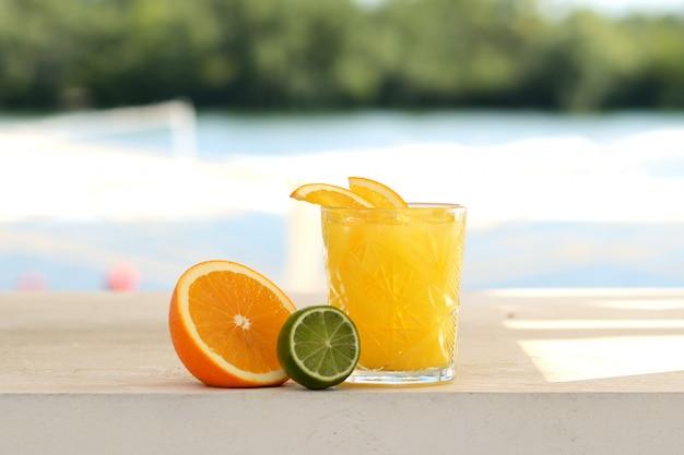 Cóctel amarillo con naranja, lima y hielo en un vaso de vidrio.