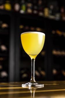 Un cóctel amarillo en un vaso de mella y nora adornado con cilantro en el bar.