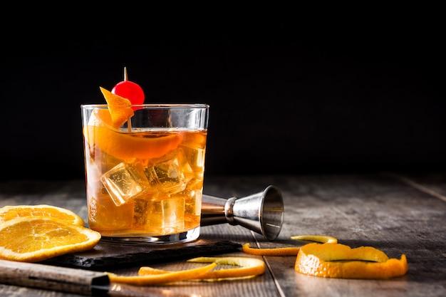 Cóctel antiguo con naranja y cereza en mesa de madera