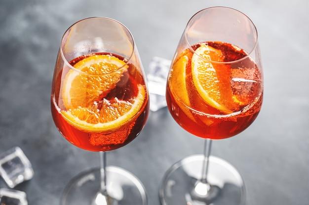 Cóctel de aperol spritz con rodajas de naranja servido en vasos