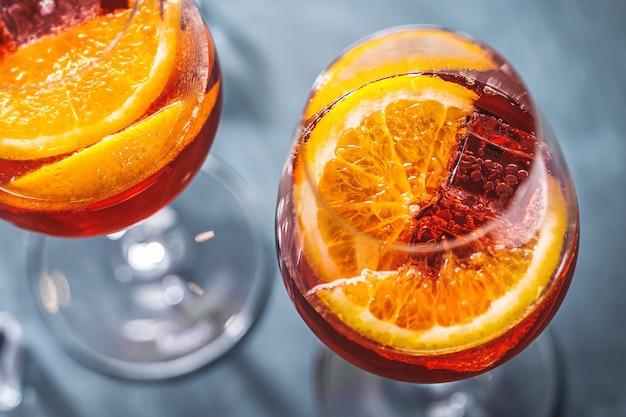 Cóctel de aperol spritz con rodajas de naranja servido en vasos.