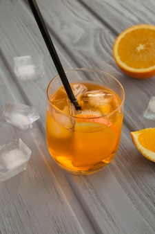 Cóctel aperol spritz en el vaso sobre la mesa de madera gris. de cerca.