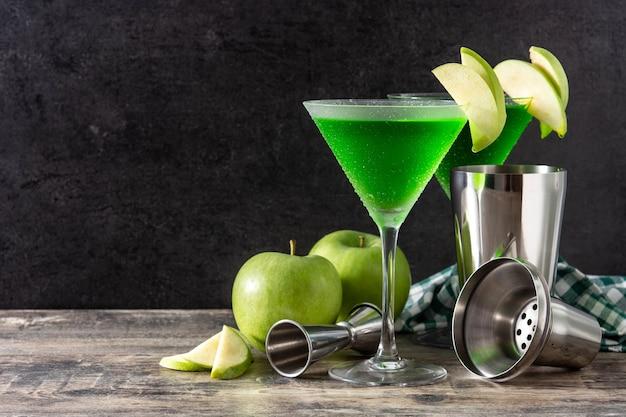 Cóctel appletini verde en vidrio sobre mesa de madera