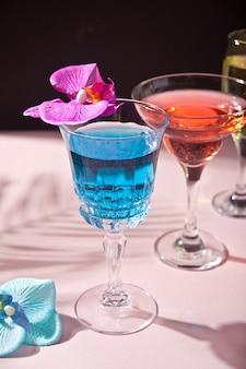 Cóctel azul y azul tropical de verano decorado con flores de orquídeas moradas y azules.