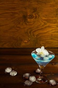 Cóctel azul en una copa de martini con orquídea blanca, vertical, espacio de copia