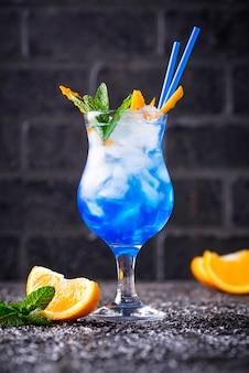 Cóctel azul con hielo y naranja.