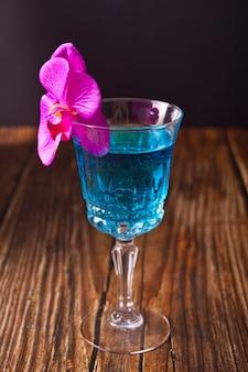 Cóctel azul tropical de verano decorado con flores de orquídeas moradas en el fondo de madera.