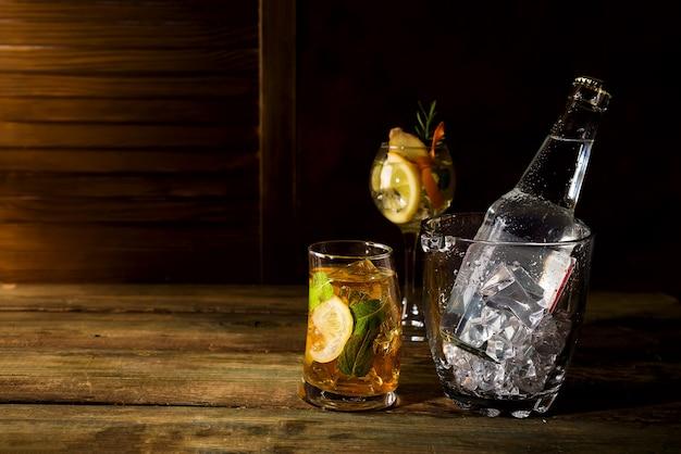 Cóctel a base de whisky con cubeta de hielo de vidrio sobre fondo de madera oscuro