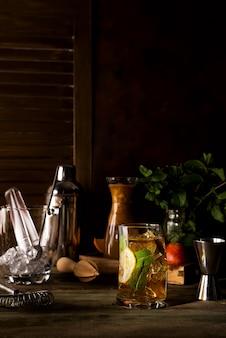 Cóctel a base de whisky en fondo de madera oscuro