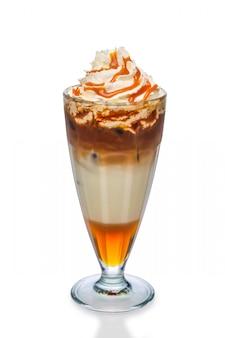 Cóctel con café, jarabe de caramelo y crema batida aislado en blanco