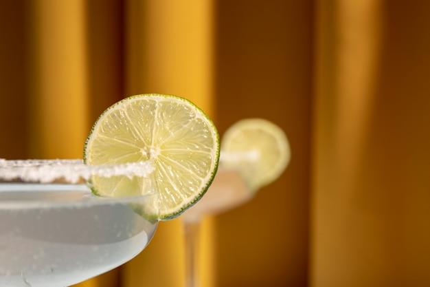 Cóctel clásico de margarita con borde salado y limas