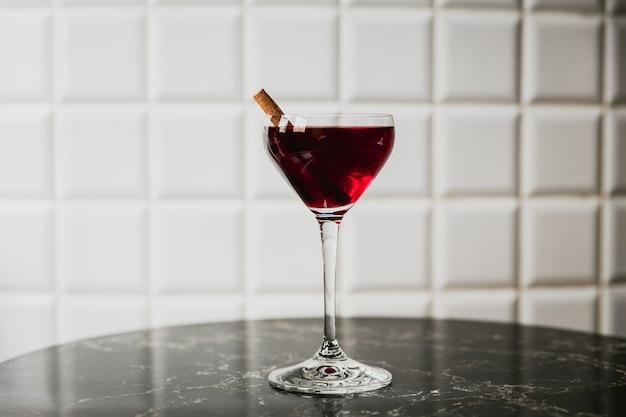 Un cóctel de color rojo oscuro en una copa nick y nora adornado con canela