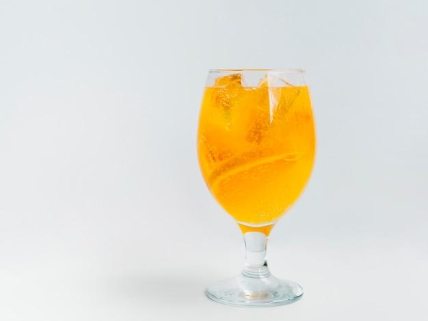 Cóctel espumoso con rodajas de naranja y cubitos de hielo.