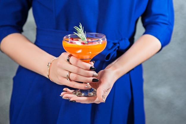 El cóctel exótico y las manos femeninas.