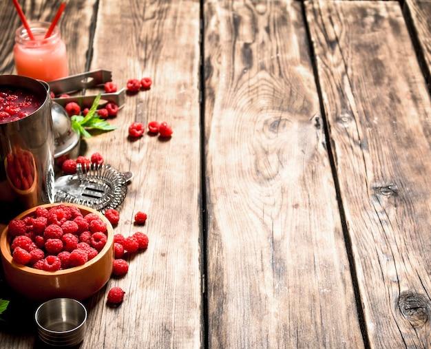 Cóctel de frambuesas silvestres en una coctelera. sobre una mesa de madera.
